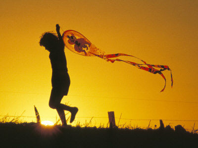 child-flying-a-kite-at-sunset